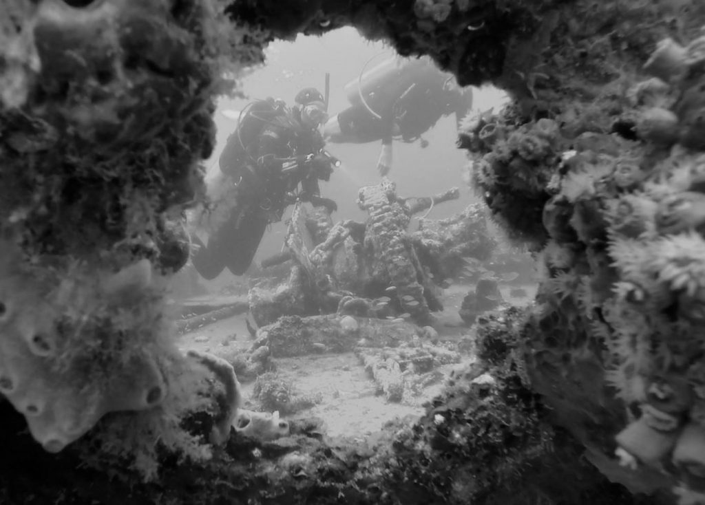 black-and-white 'through the porthole' image of divers on a wreck.