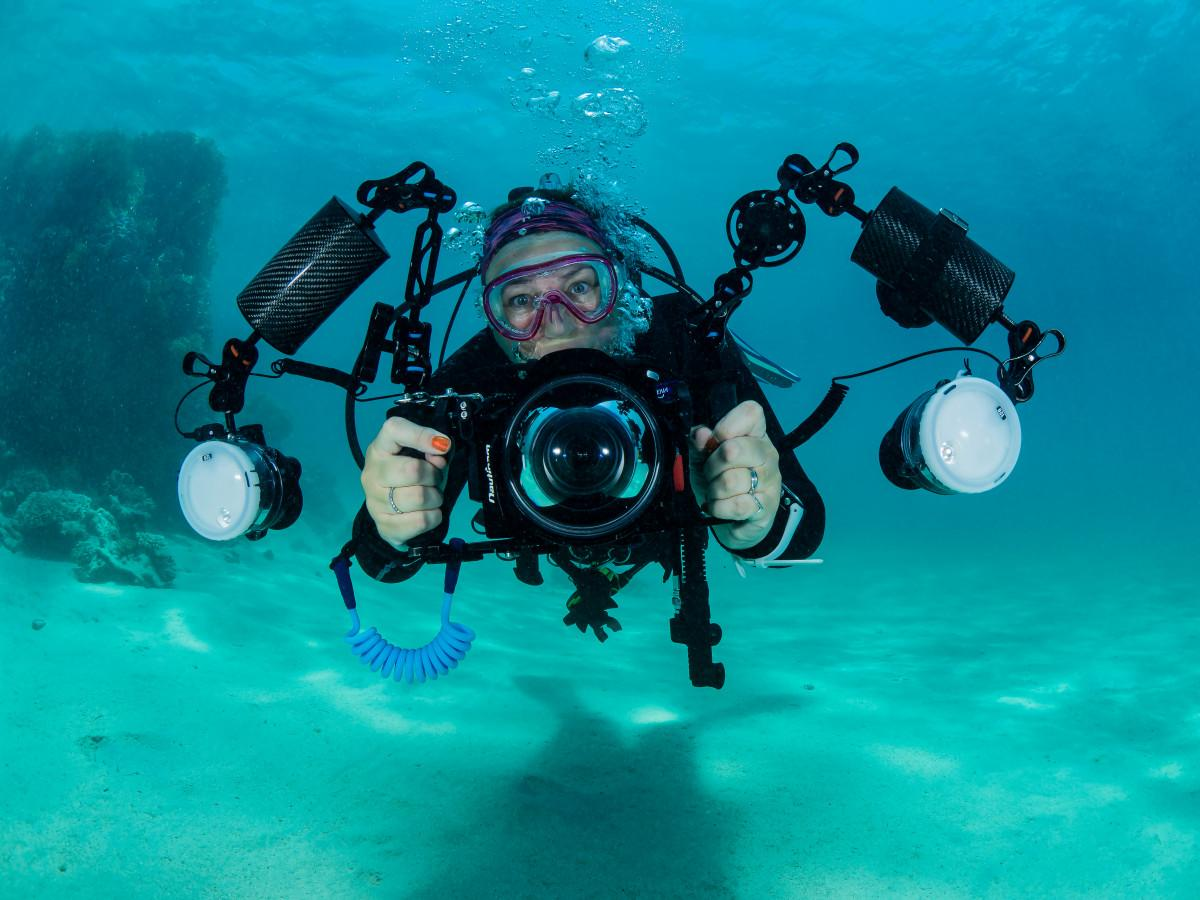 scubadiver with camera equipment