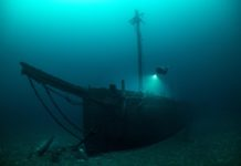 The Typo sank in a collision in 1899 while carrying coal. This three-masted schooner now sits in deep water with it's forward mast still standing up into 110ft of water. The bow sprit is intact with rigging and the bell is still in place. CCR diver Jim Eckhoff illuminates one of it's wood stock anchors on the bow.